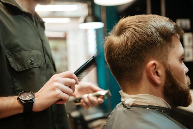 Zdjęcie młodego człowieka coraz fryzura przez fryzjera z brzytwą siedząc w fotelu. spójrz na bok.