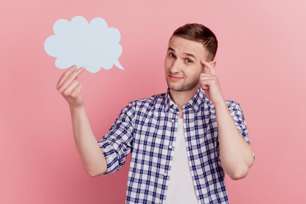 Zdjęcie młodego człowieka, który myśli, że głębokie kreatywne wątpliwości trzymają okno dialogowe mowy w chmurze papieru na białym tle nad pastelowym kolorem tła