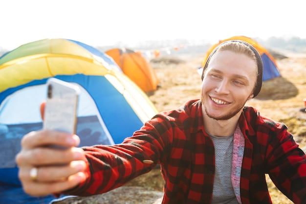 Zdjęcie młodego człowieka na zewnątrz w bezpłatne alternatywne wakacje na kempingu nad górami za pomocą telefonu komórkowego weź selfie.