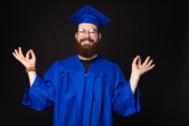 Zdjęcie młodego człowieka studenta w niebieskim kawalerem, pokazując gest zen