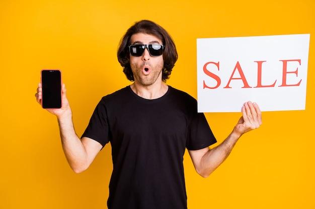 Zdjęcie młodego człowieka trzymać telefon papierowy plakat pusta przestrzeń otwarte usta nosić czarną koszulkę okulary przeciwsłoneczne na białym tle żółty kolor tła