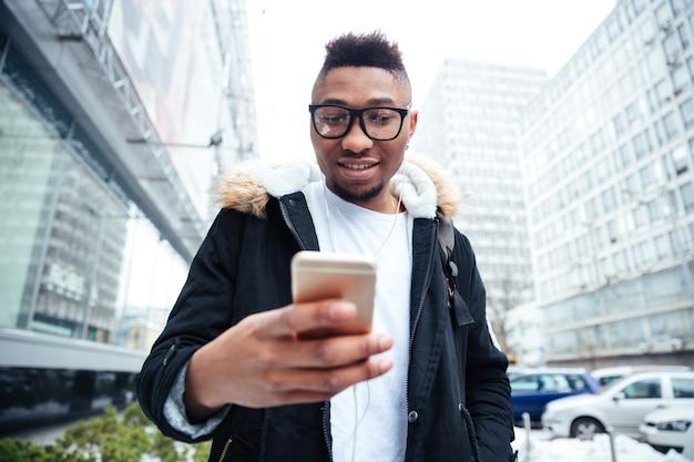 Zdjęcie młodego człowieka trzymającego telefon w ręce i rozmawiając podczas słuchania muzyki na świeżym powietrzu.