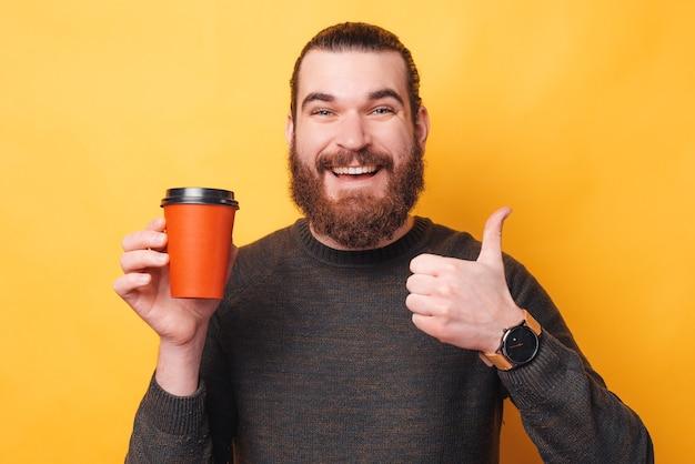 Zdjęcie młodego mężczyzny brodaty hipster pokazując kciuk na żółtej ścianie