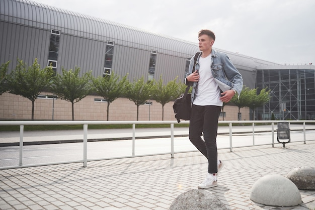 Zdjęcie młodego mężczyzny przed ekscytującą podróżą na lotnisku.