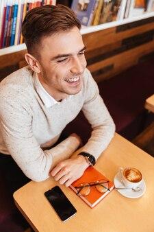 Zdjęcie młodego mężczyzny szczęśliwy ubrany w koszulę, siedząc w kawiarni z filiżanką kawy i książki. patrząc na bok.