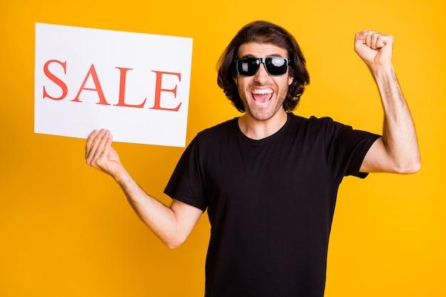Zdjęcie młodego mężczyzny trzyma pokazując papierową afisz otwarte usta podnieś rękę nosić t-shirt okulary przeciwsłoneczne na białym tle żółty kolor tła