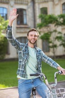 Zdjęcie młodego mężczyzny w koszuli w kratę na rowerze