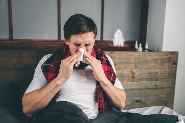 Zdjęcie młodego mężczyzny z chusteczką. chory leży w łóżku i ma katar. człowiek leczy na przeziębienie. model mężczyzna ma wysoką temperaturę, ból głowy, migrenę