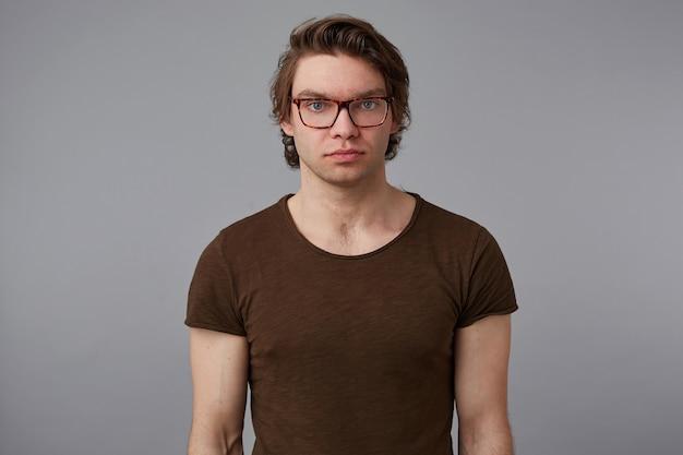 Zdjęcie młodego poważnego faceta w okularach nosi pustą koszulkę, stoi na szarym tle i patrzy w kamerę bez emocji.