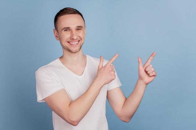 Zdjęcie młodego przystojnego mężczyzny pokazuje punkt wskazujący palec pusta przestrzeń reklama promo rekomendacja na białym tle nad niebieskim kolorem tła