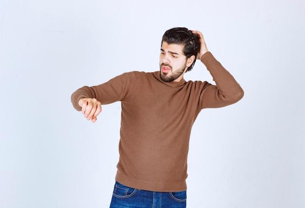 Zdjęcie młodego, przystojnego mężczyzny stojącego modelu i wskazującego na jego rękę. zdjęcie wysokiej jakości