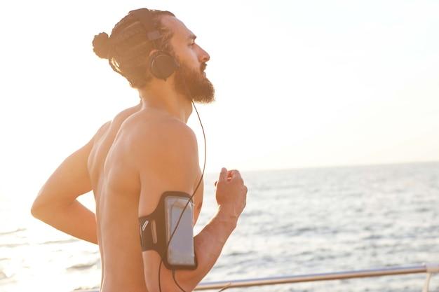 Zdjęcie młodego przystojnego, sportowego brodatego faceta, posłuchaj ulubionego miksu na słuchawkach i biegania nad morzem. ciesz się porankiem i żartem.