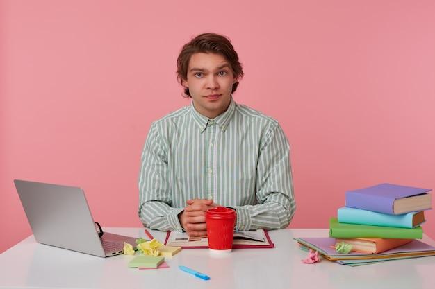 Zdjęcie młodego spokojnego faceta w okularach, siedzącego przy stole z książkami, pracującego na laptopie, poważny patrzy w kamerę, na białym tle nad różowym tłem.