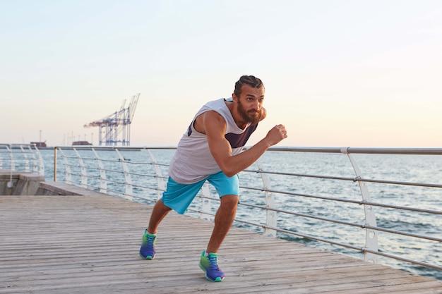 Zdjęcie młodego sportowca brodaty biegnący mężczyzna nad morzem i rano sport.