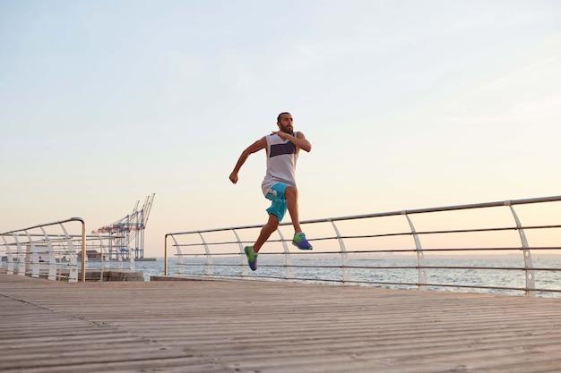 Zdjęcie młodego sportowego przystojnego brodacza biegnącego faceta robi poranne ćwiczenia nad morzem, rozgrzewka przed biegiem.