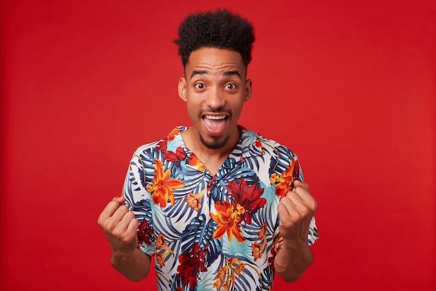 Zdjęcie młodego szczęśliwego afroamerykanina, ubranego w hawajską koszulę, patrzy w kamerę z szeroko otwartymi ustami, zaciska pięści i raduje się ze zwycięstwa, stoi na czerwonym tle.