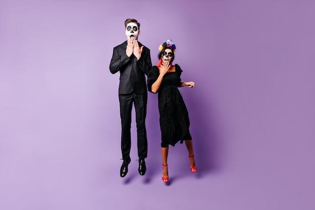 Zdjęcie młodego, szczupłego chłopaka i dziewczyny z pomalowanymi twarzami w czarnych strojach. para z meksyku patrząc zaskoczona w kamerę, skacząc na odosobnionym tle.
