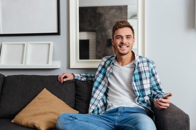 Zdjęcie młodego uśmiechniętego mężczyzny ubranego w koszulę w nadruk klatki, siedzącego na kanapie w domu i patrzącego na kamerę