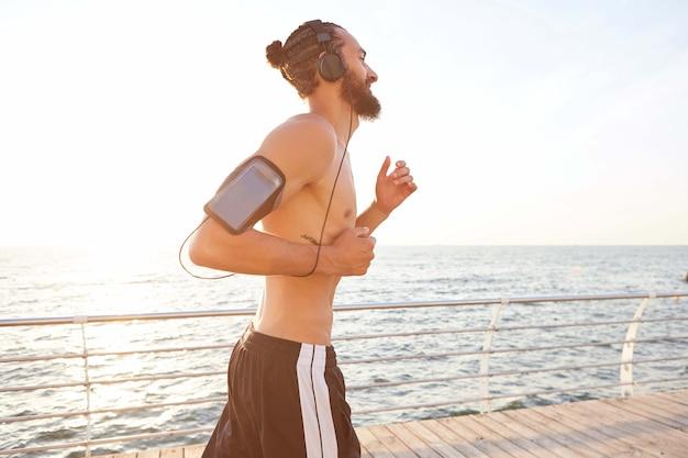 Zdjęcie młodej atrakcyjnej, sportowo-brodatej mguy, biegnącej rano nad morzem, słuchającej ulubionego miksu na słuchawkach.