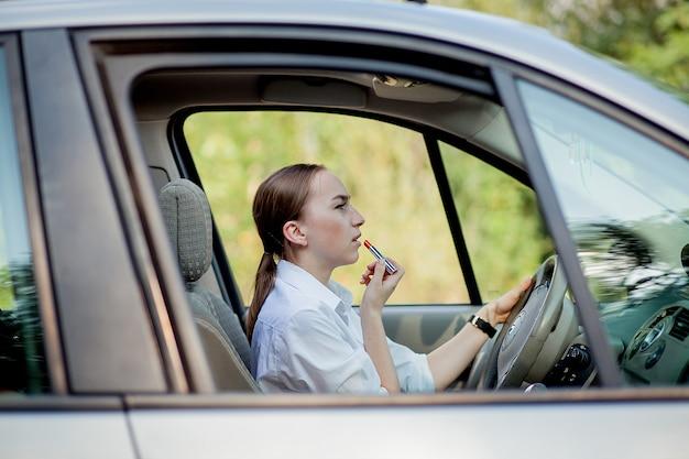 Zdjęcie młodej bizneswoman robi makijaż podczas prowadzenia samochodu w korku.