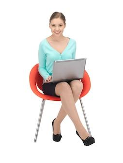 Zdjęcie młodej bizneswoman siedzącej na krześle z laptopem