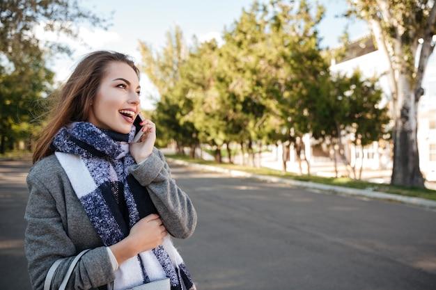 Zdjęcie młodej damy niesamowite rozmawia przez telefon spójrz na bok.