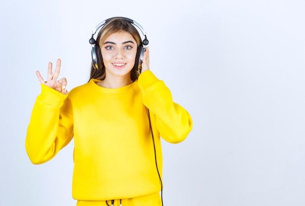 Zdjęcie młodej dziewczyny w słuchawkach robi ok znak i patrzy na kamerę