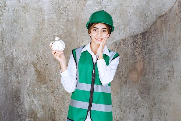 Zdjęcie młodej dziewczyny w zielonej kamizelce i kasku trzymającej budzik