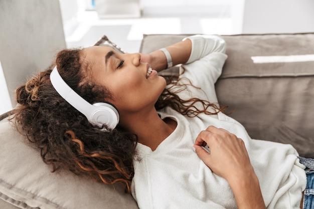 Zdjęcie młodej kobiety afroamerykanów, słuchanie muzyki za pomocą słuchawek bezprzewodowych, leżąc na kanapie w domu