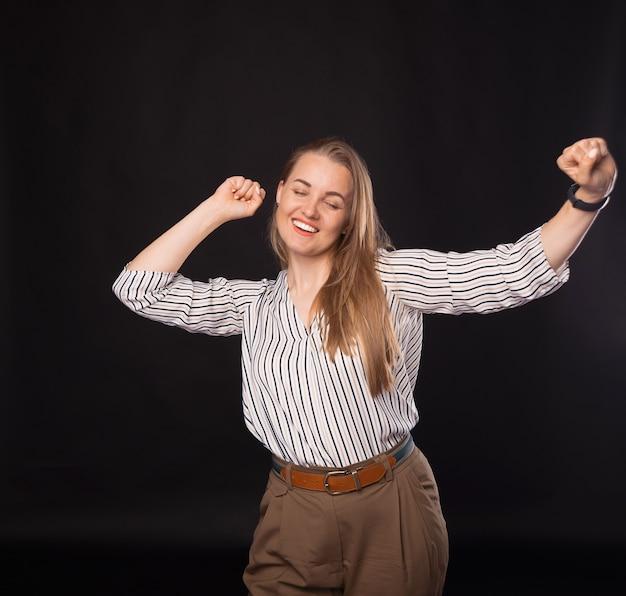 Zdjęcie młodej kobiety biznesu świętującej zwycięstwo na ciemnym tle