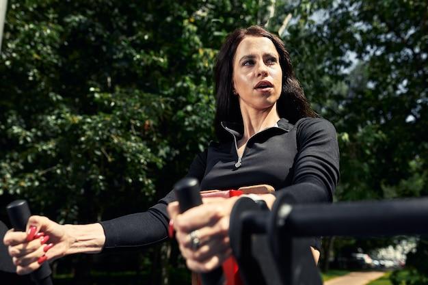 Zdjęcie młodej kobiety europejskiej na ulicznym treningu w parku sportowym w słoneczny dzień