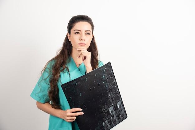 Zdjęcie młodej kobiety lekarza trzymającego prześwietlenie nad białą ścianą.