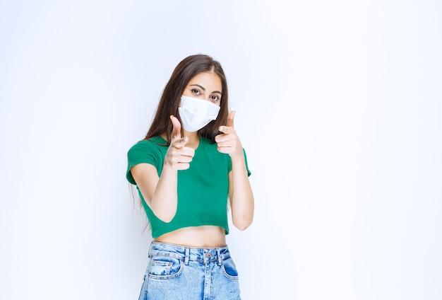 Zdjęcie młodej kobiety modelu w ochronnej masce medycznej, wskazując na aparat.