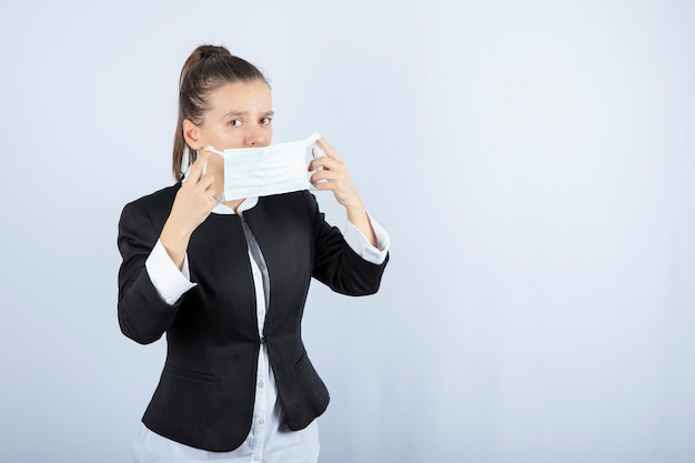 Zdjęcie młodej kobiety noszącej maskę medyczną na białym tle. wysokiej jakości zdjęcie