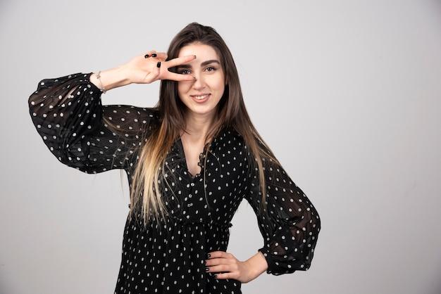 Zdjęcie młodej kobiety noszącej sukienkę, uśmiechając się i pokazując znak pokoju.
