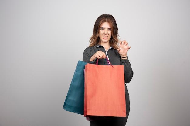 Zdjęcie młodej kobiety trzymającej torby na zakupy.