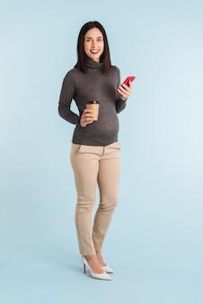 Zdjęcie młodej kobiety w ciąży na białym tle przy użyciu telefonu komórkowego.