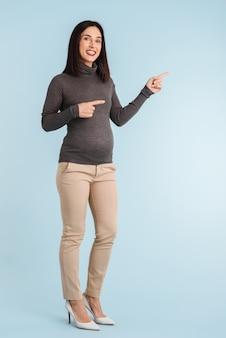 Zdjęcie młodej kobiety w ciąży na białym tle, wskazując na copyspace.