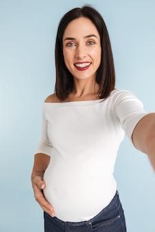 Zdjęcie młodej kobiety w ciąży na białym tle wziąć selfie