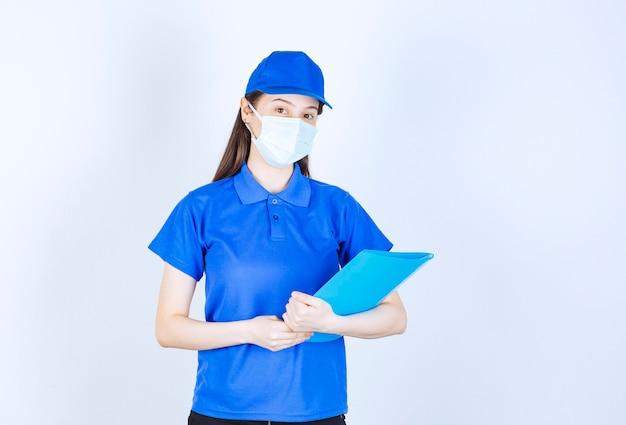 Zdjęcie młodej kobiety w masce medycznej stojącej i trzymającej folder.