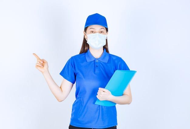 Zdjęcie młodej kobiety w masce medycznej trzymając folder i wskazując palcem na bok.