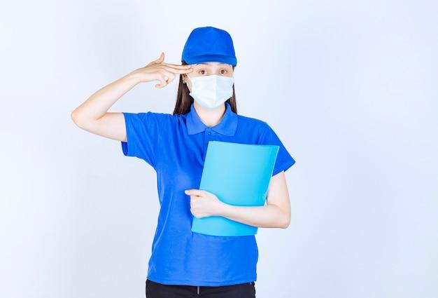 Zdjęcie młodej kobiety w masce medycznej, trzymając folder i wskazując palcem na jej głowę.