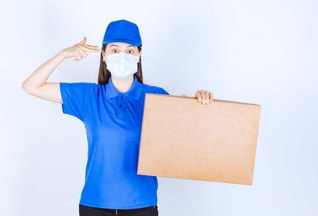 Zdjęcie młodej kobiety w mundurze i masce medycznej, trzymając papierowe pudełko.
