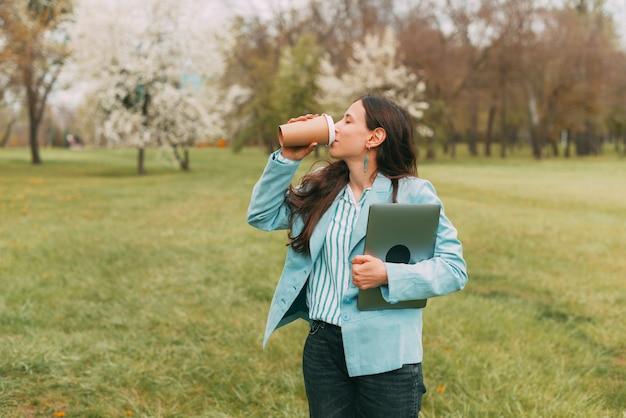Zdjęcie młodej kobiety w swobodnej pozycji w parku i picia filiżanki kawy