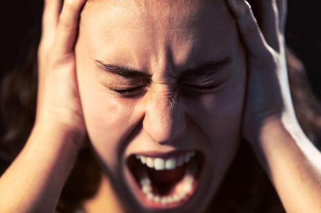 Zdjęcie młodej kobiety z bliska krzyczy na czarnym tle. koncepcja choroby psychicznej.