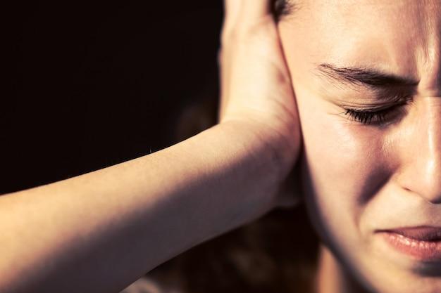 Zdjęcie młodej kobiety z bliska z bólem głowy na czarnym tle. koncepcja choroby psychicznej.