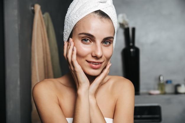 Zdjęcie młodej kobiety z ręcznikiem na głowie, dotykając jej twarzy po kąpieli