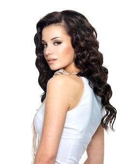 Zdjęcie młodej kobiety z uroda długie kręcone włosy. modelka - portret widok z boku.