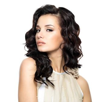 Zdjęcie młodej kobiety z uroda długie kręcone włosy. modelka pozowanie studio.