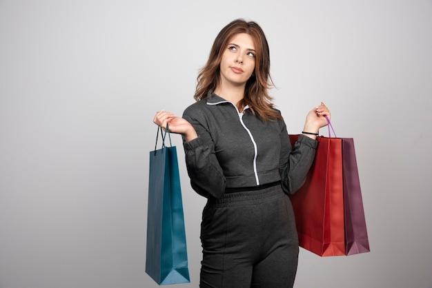Zdjęcie młodej kobiety zamyślony, trzymając torby na zakupy.